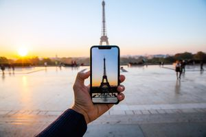 iPhone held in hand taking picture of Eiffel Tower