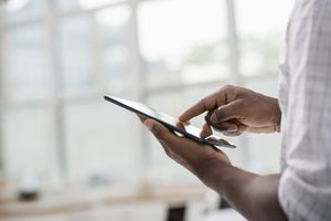 Close-up of man using touchscreen tablet