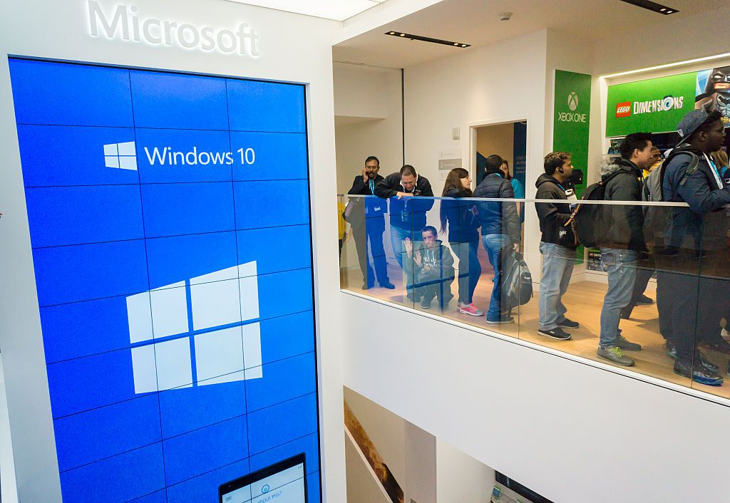 Line of people standing in Windows store next to sign that says Windows 10