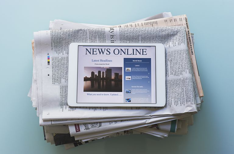 Digital newspaper displayed on tablet, on top of printed newspapers