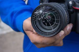 Man holding a broken camera with cracked lens