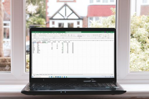 A windows laptop sitting on a window sill, displaying Microsoft Excel.