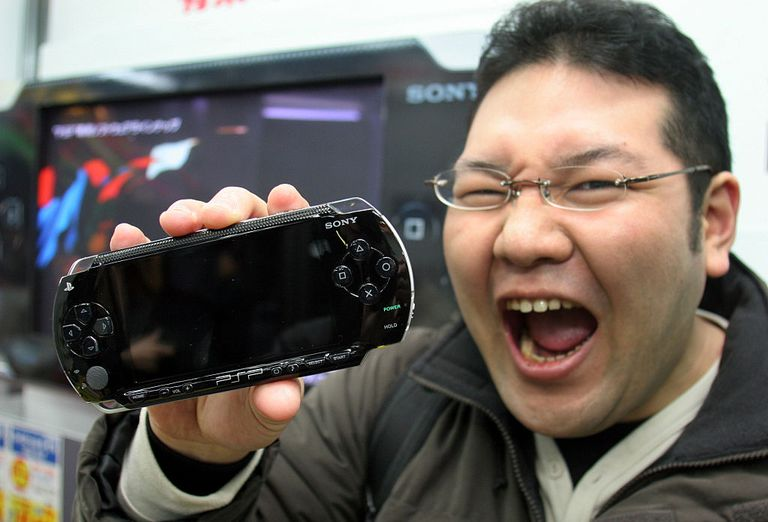 A man holds a Sony PlayStation Portable (PSP)