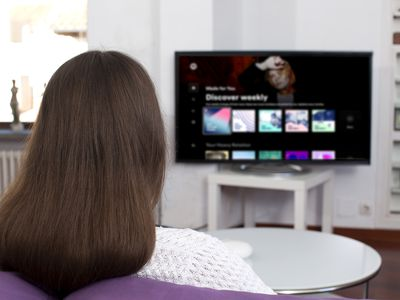 A woman watching her TV with Spotify playing on it via an Amazon Firestick.