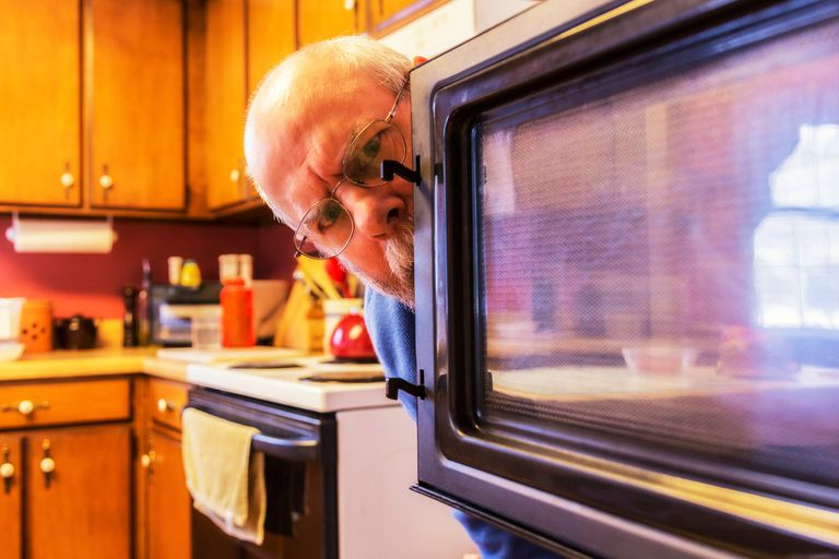 Man peeking carefully into microwave oven because he fears his smart devices are spying on him
