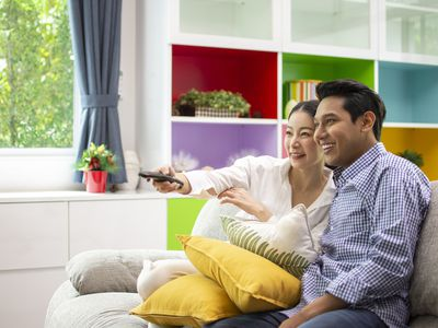 A couple sitting on a sofa smiling at an off-camera TV