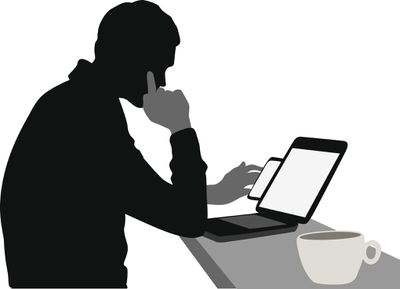Shadowed figure looking at a laptop and a smartphone.