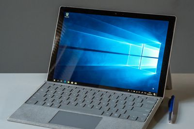 A Microsoft Surface Pro sitting on a desk with keyboard attached