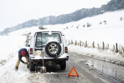 Man changing a flat tire in the snow