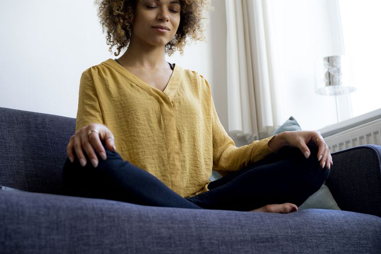 woman sitting on couch meditating