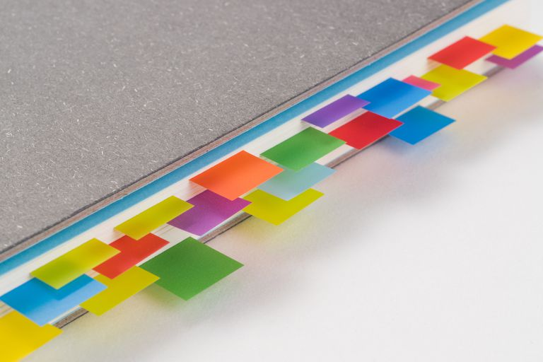 Multi Colored Adhesive Notes in Books on White Background