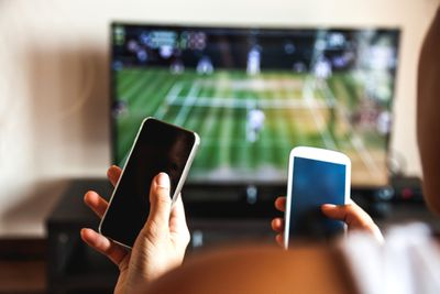 Two people holding smartphones while watching TV