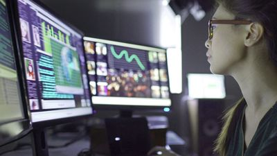 Woman sitting at desk and surrounded by 3 large computer monitors displaying many open apps