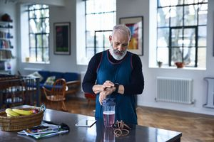 A man standing in his kitchen looking at his smartwatch