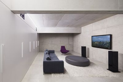 A modern living room with wall-mounted TV, stereo speakers, and a couch
