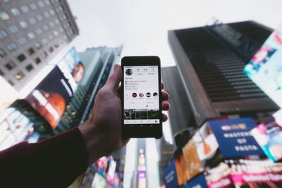 Person holding a smartphone with an Instagram profile open on the screen.