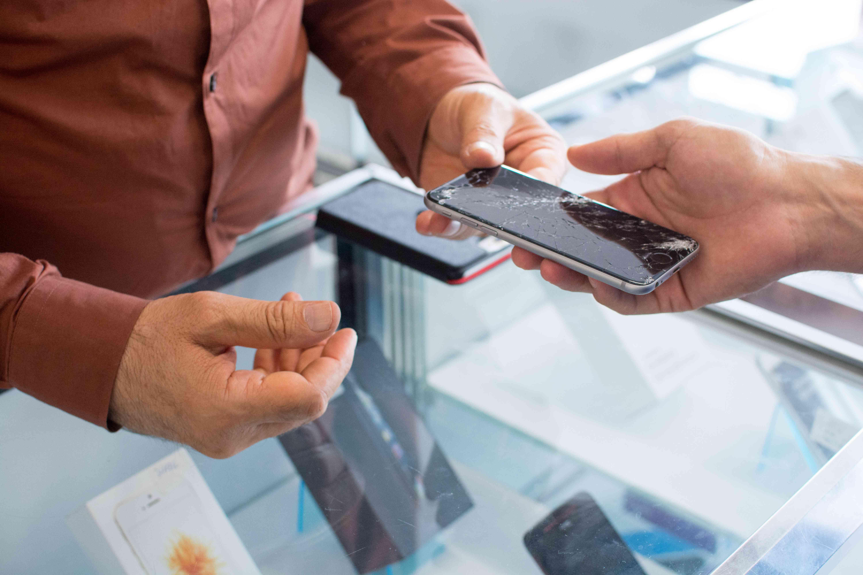 Someone handing a broken smartphone to a repair person.