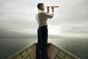 Man in boat looking through spyglass