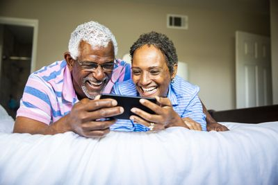 Two smiling people watching something on their iPhone