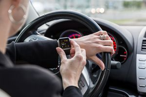 Woman checking her Apple Watch in a car