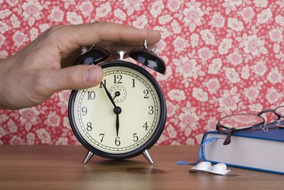 A human hand pressing an old-fashioned alarm clock
