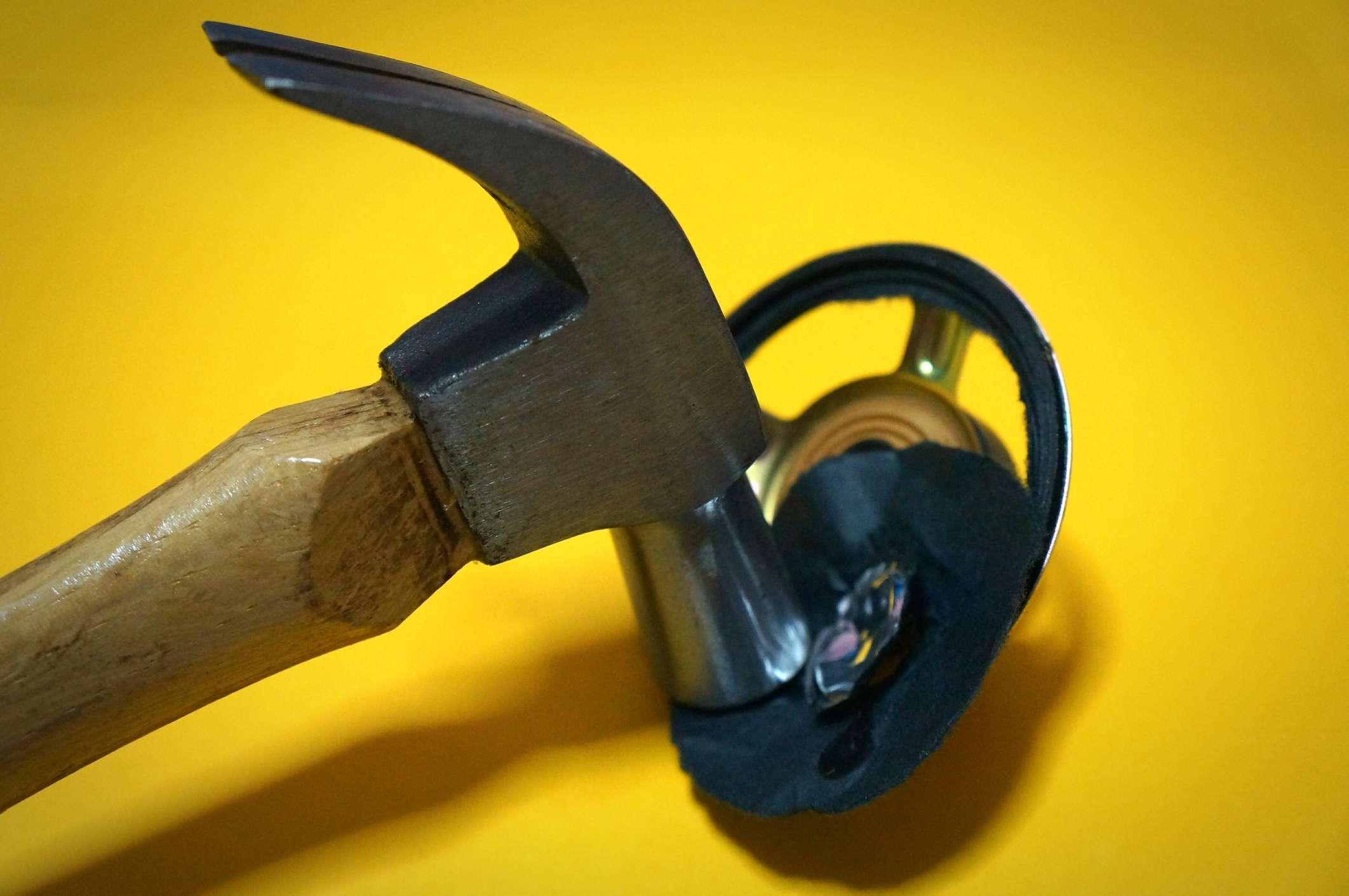 A hammer hitting a speaker cone.