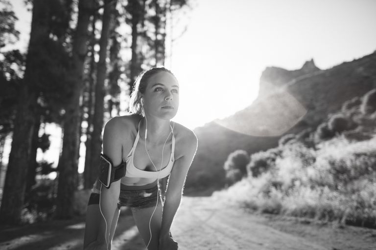 Grayscale image of a runner getting ready to go