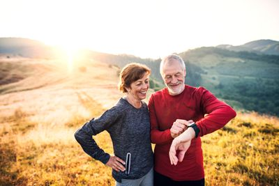 An older couple on a hill in the countryside looking at a smartwatch