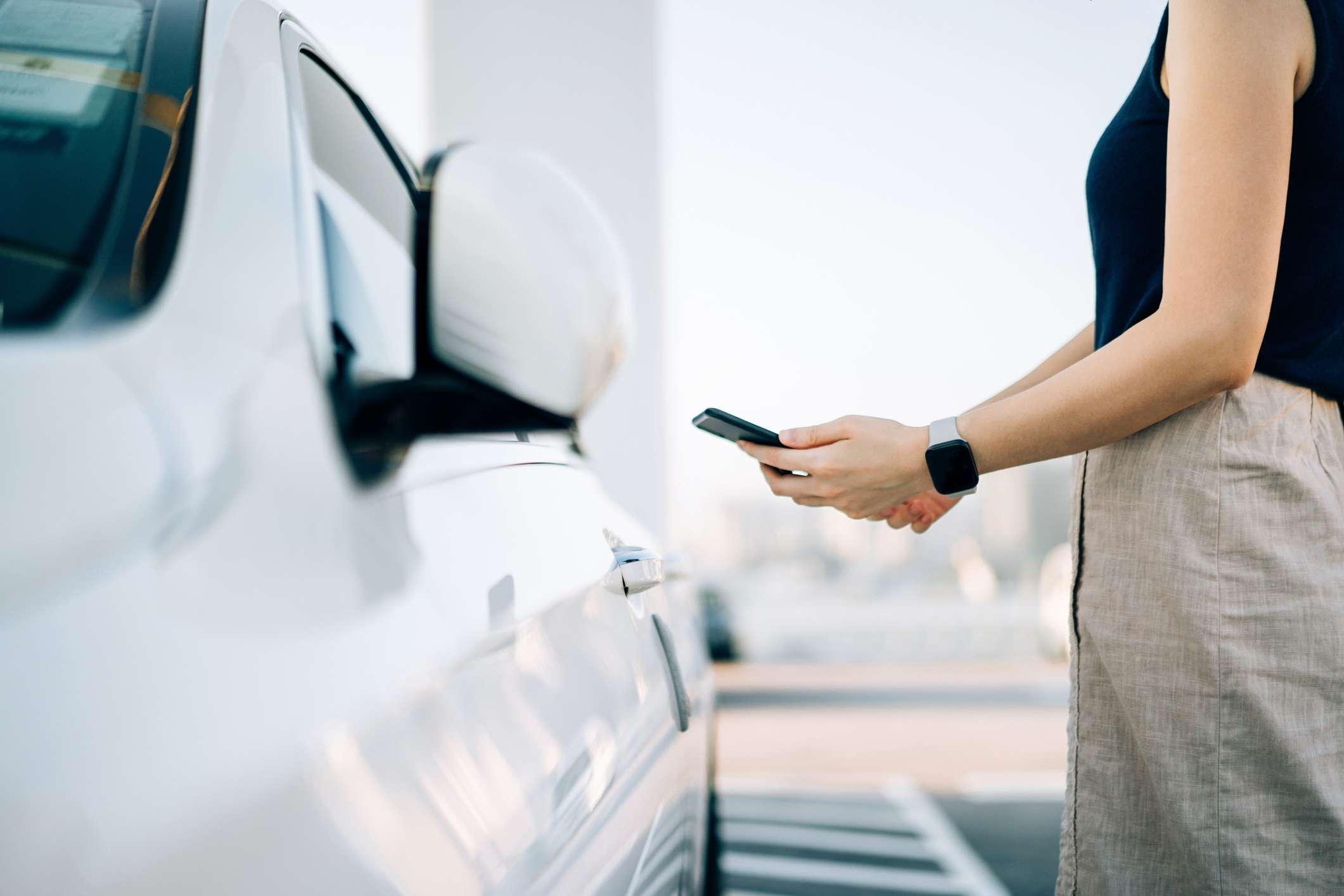 woman unlocking car door with smartphone