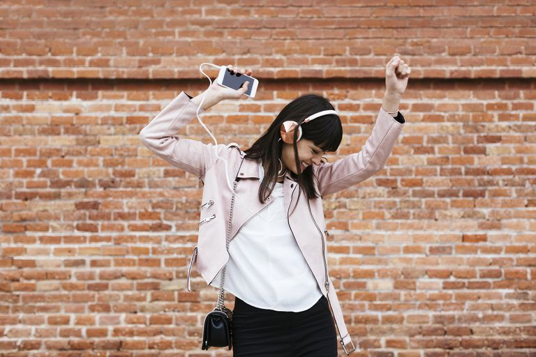 Happy woman with cell phone listening to music on headphones at brick wall