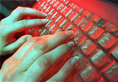 Fingers typing on a keyboard with red backglow