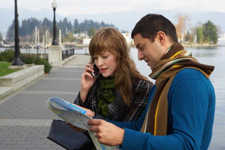 Couple reading map on waterfront, young woman using mobile phone