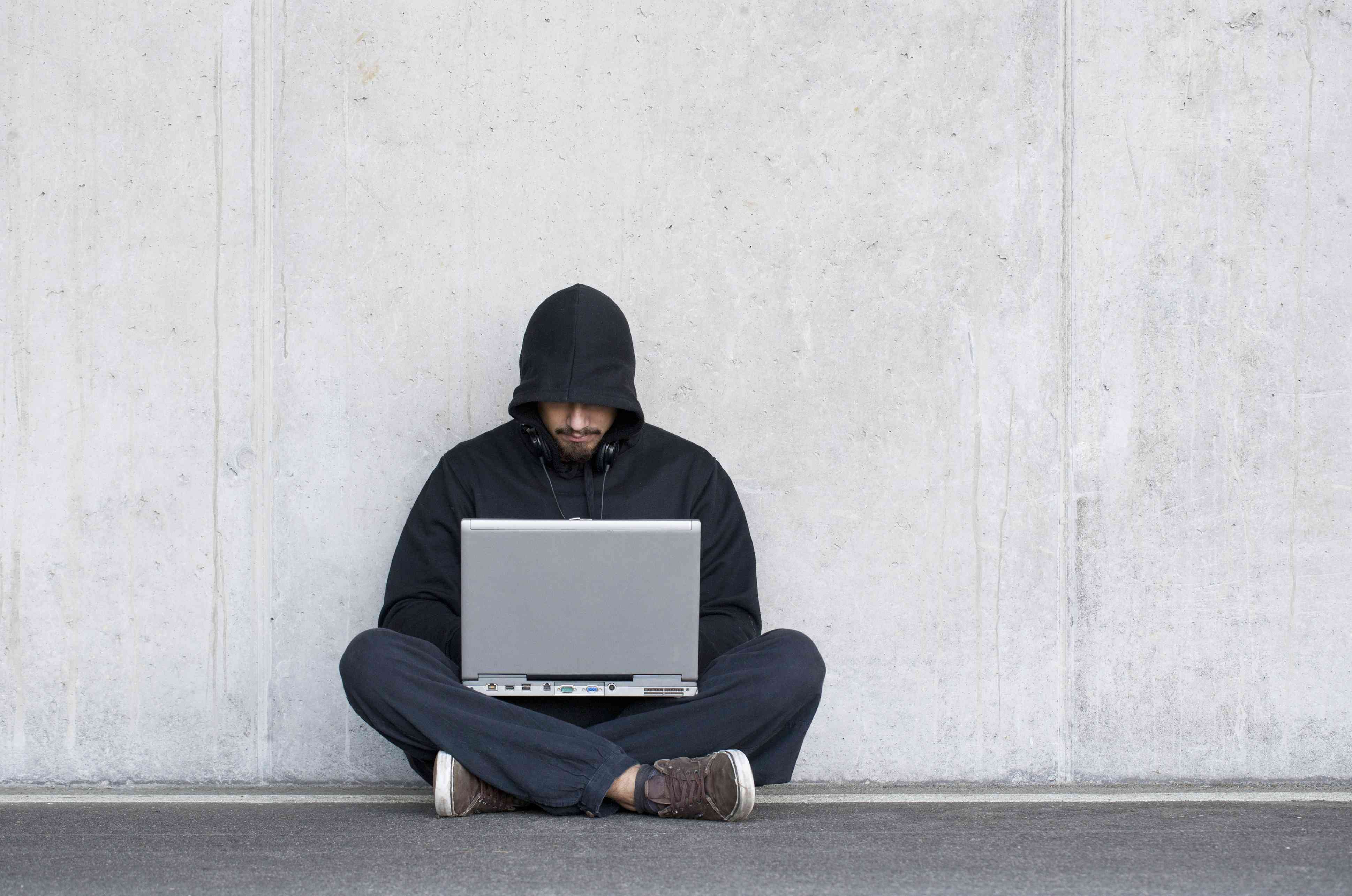 Person sitting against concrete wall wearing a hoodie and using a laptop.