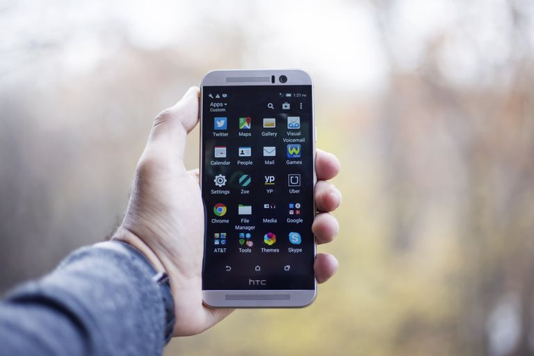 Hand holding an HTC smartphone.