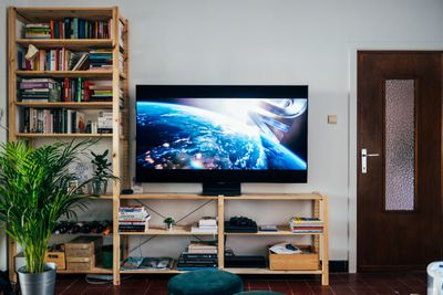 Television set on top of bookshelf playing a movie