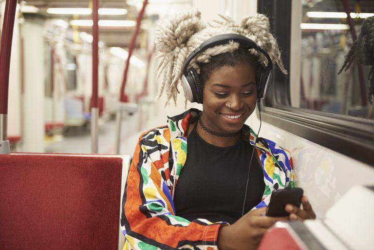 Woman listening to headphones in subway