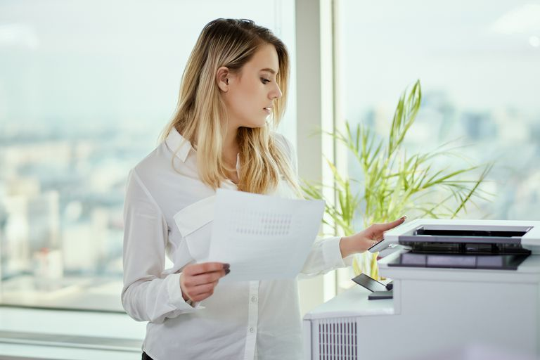 Woman in an office holding papers while using a printer.