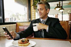 Hispanic businessman using cell phone in restaurant