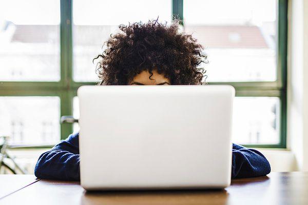 Woman working behind laptop