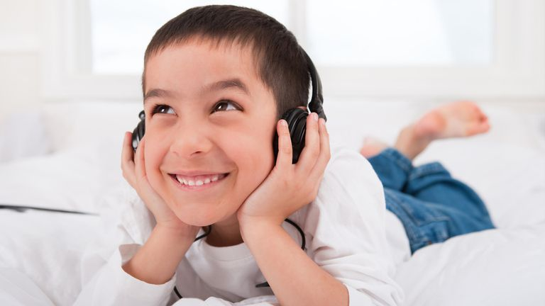 Boy laying down listing to headphones