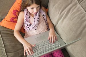 Young girl using laptop on sofa