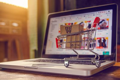 Laptop with tiny shopping cart in front illustrating online shopping