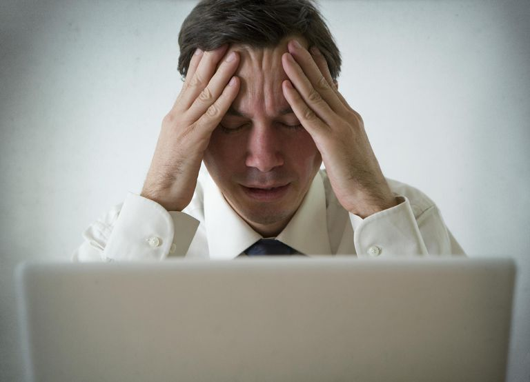 Picture of a man sitting at a laptop, looking stressed