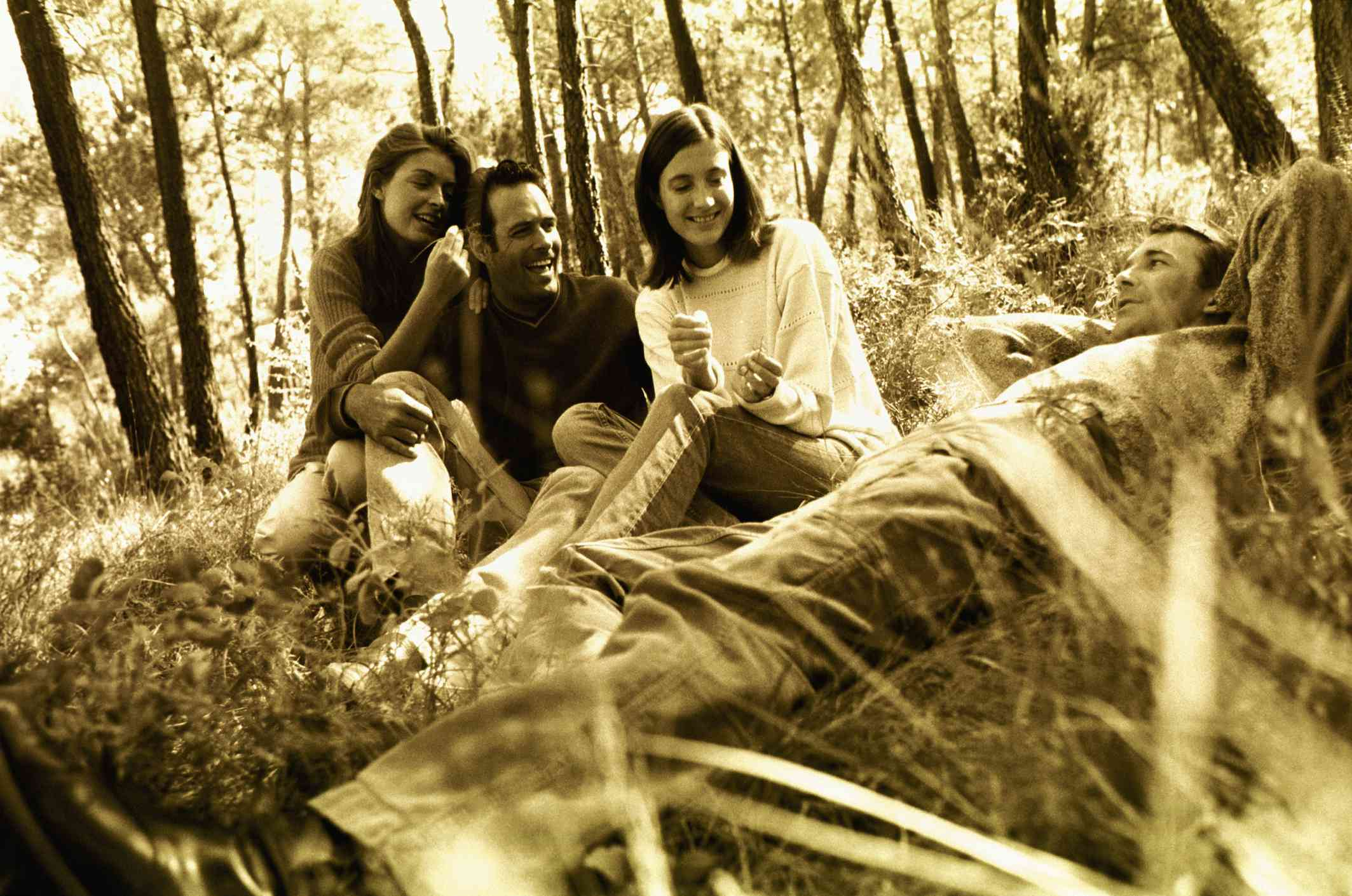 A yellow monochrome image of a group of friends sitting in the woods together.