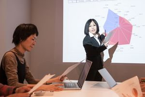Two women in a meeting during a presentation.