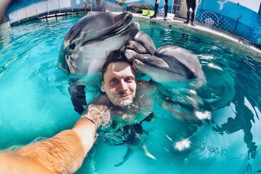 Man using a GoPro to capture images of swimming with dolphins.