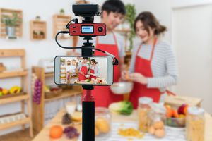 Closeup smart mobile phone filming couple cooking in the kitchen