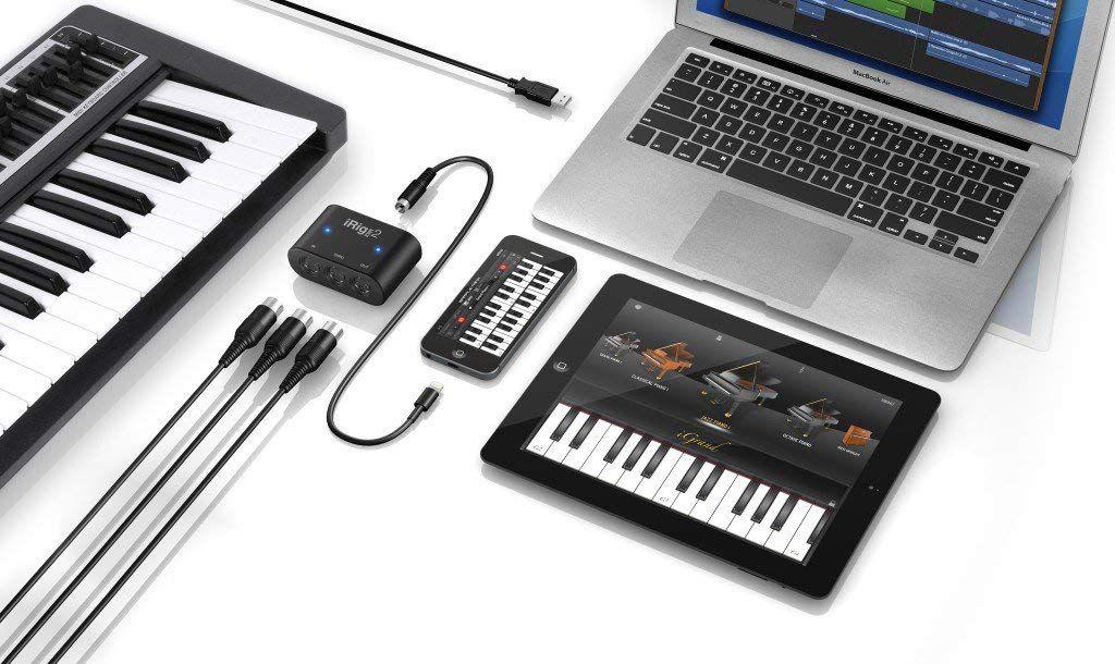 iRig MIDI 2 next to keyboard, iphone, ipad, and laptop