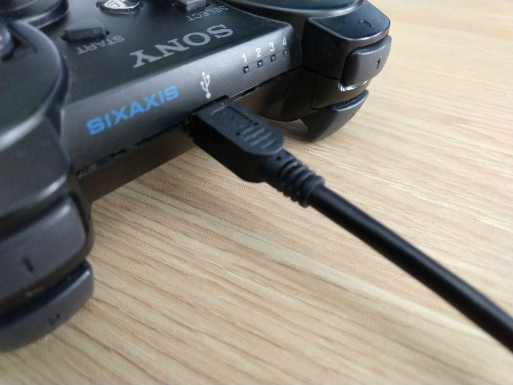 A PS3 plugged in with a mini USB cable