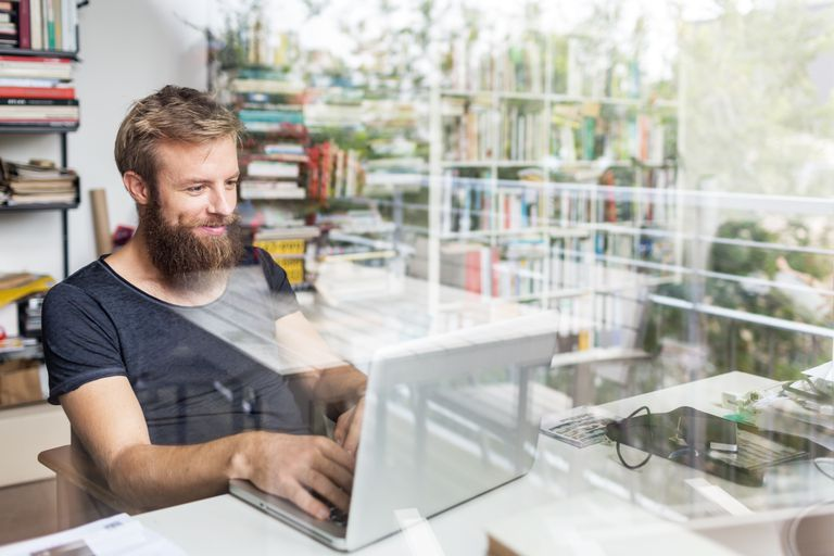 Young Bearded Man Working At Home Office